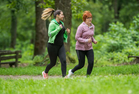 sun energy: Mother and daughter wearing sportswear and running in green forest at mountainduring spring Stock Photo