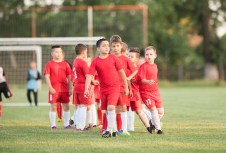 warming up: Kids soccer football - small children players exercising before match on soccer field Stock Photo