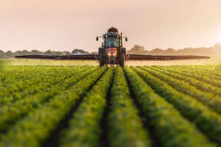 Tractor sproeien pesticiden op sojabonen veld met spuit op de lente