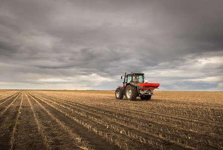 Tractor spreading artificial fertilizers  in field Stok Fotoğraf
