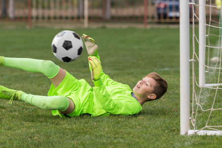 Little goalkeeper used hands for catches the ball in match game Stock Photo