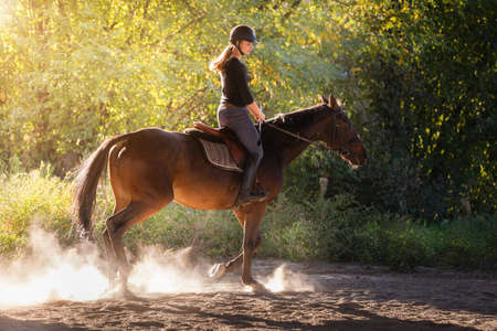 Young pretty girl - riding a horse with backlit leaves behind