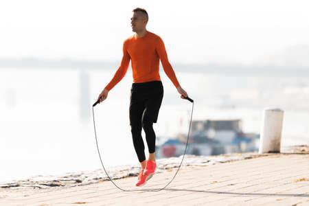 beau jeune homme portant des vêtements de sport et saut de corde à roulettes pendant l & # 39 ; automne Banque d'images