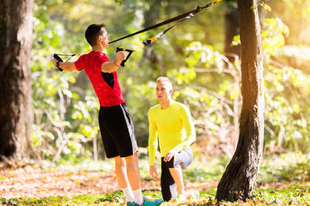 Handsome young men wearing sportswear and exercising in forest at mountain during autumn Stock Photo