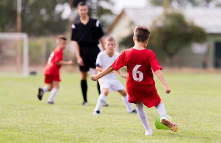 Young children players match on soccer field