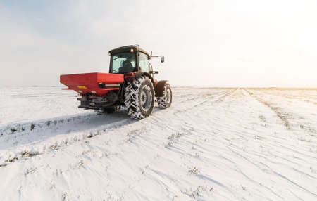 Farmer with tractor seeding - sowing crops at agricultural fields in winter - snow