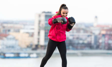 Young pretty girl wearing boxing gloves throwing a punch - martial arts training Archivio Fotografico