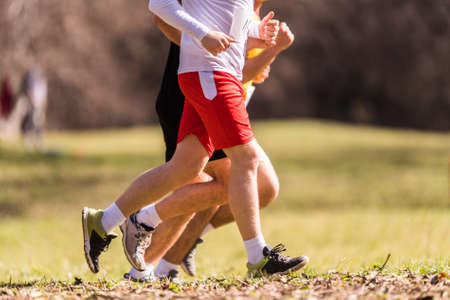 Marathon running race, people feet on grass road