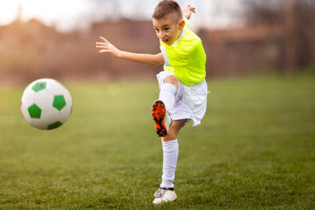 Boy kicking football on the sports field during soccer match