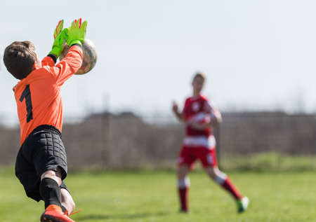 Young Boy Goalkeeper Saving A Football In A Game Of Soccer.