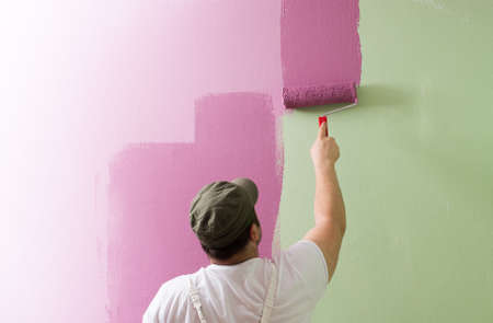 Young man is painting wall with painting roller