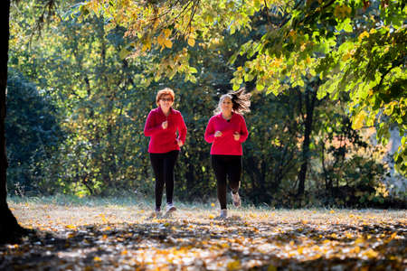 Mother and daughter wearing sportswear and running in forest at mountain