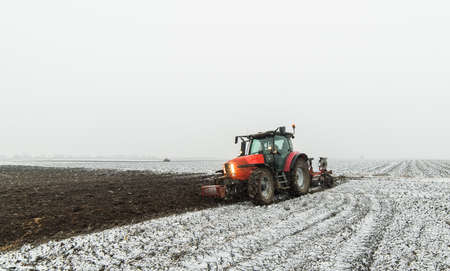 Tractor plowing a field in winter