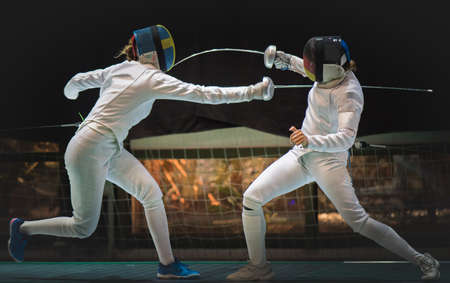 Two man fencing athletes fight on professional sports arena Stock Photo