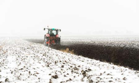 Traktor orze pole zimą