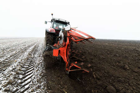 Tractor plowing a field in winter Stock Photo - 119386065