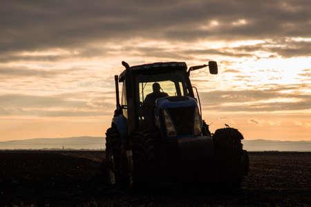 Farmer plowing stubble fields Reklamní fotografie - 119386576