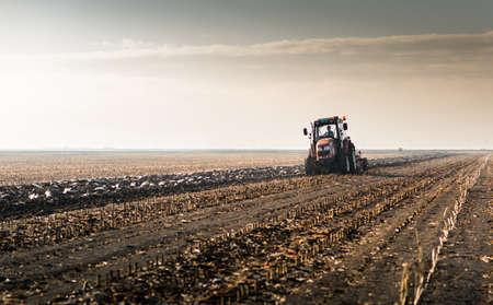 Tractors plowing stubble fields Reklamní fotografie - 120588840