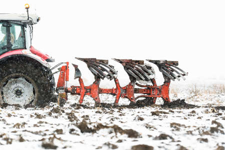 Tractors plowing stubble fields during winter Reklamní fotografie
