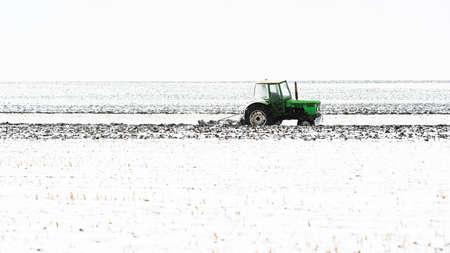 Tractors plowing stubble fields during winter Reklamní fotografie - 120588894