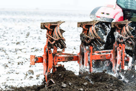 Tractors plowing stubble fields during winter Reklamní fotografie - 120588895