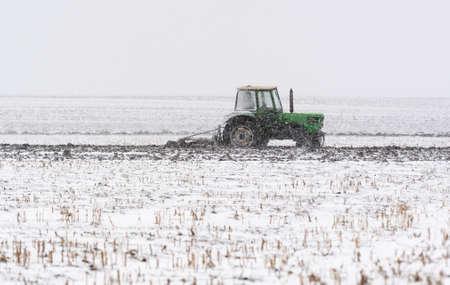 Tractors plowing stubble fields during winter Reklamní fotografie - 120588897