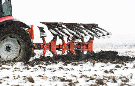 Tractors plowing stubble fields during winter