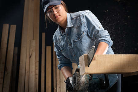 Young woman  using modern electric  saw for ctting wood  in the workshop