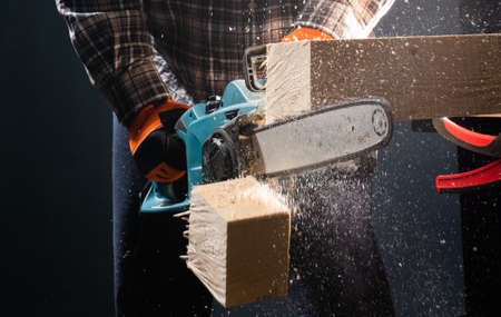 Man using modern electric circular saw for ctting wood  in the workshop