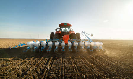 Farmer with tractor seeding crops at agricultural field