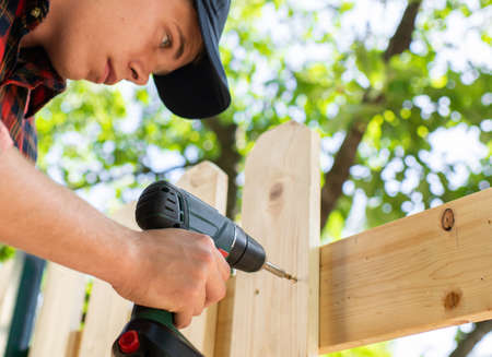 Young handsome man using electric drill on wooden fence Stockfoto