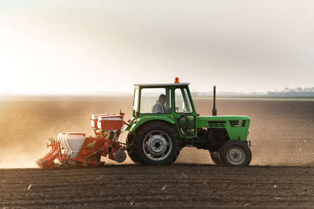 Farmer with tractor seeding  crops at agricultural field Banco de Imagens