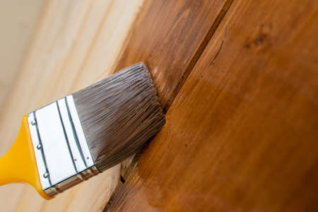 Painting teak wooden surface with a paintbrush