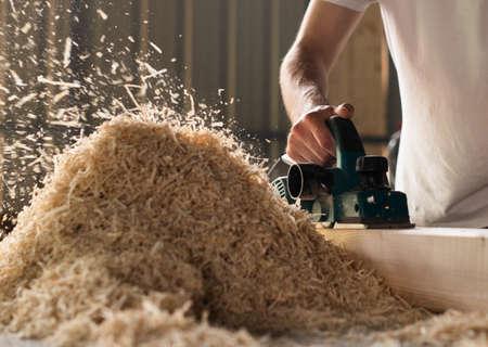 Carpenter works with electrical planer in workshop Banco de Imagens - 124967420