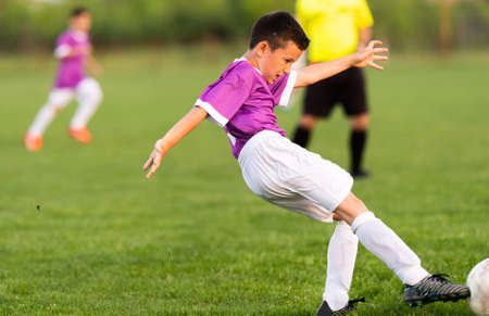 Young boys playing soccer on the green grass pitch. Stockfoto