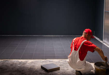 A construction worker putting on new floor tiles.