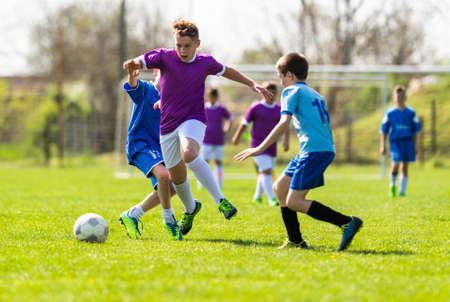 Kinderfußballfußball - kleine Kinderspieler spielen auf dem Fußballplatz