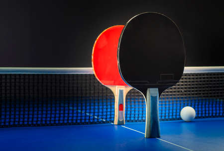 Two table tennis rackets and balls on a blue table with net.