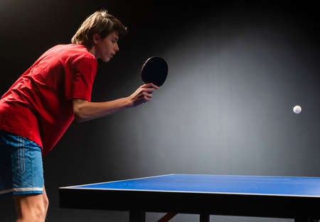 Teenager play  table tennis in on black background 스톡 콘텐츠