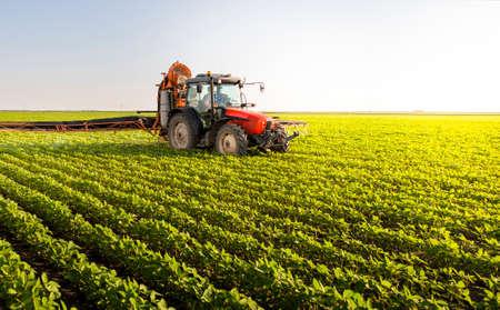 Trekker sproeien van pesticiden op sojaveld met sproeier in de lente Stockfoto