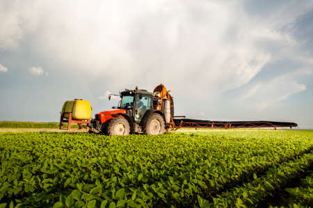 Traktor sprüht Pestizide auf Sojafeld mit Sprüher im Frühjahr Standard-Bild