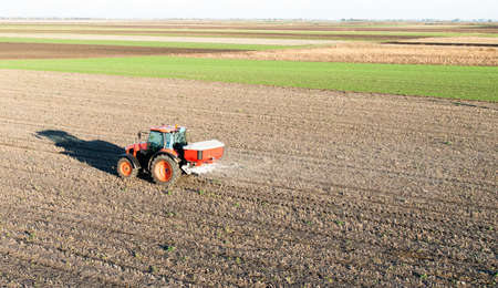 Tractor spreading artificial fertilizers  in field 스톡 콘텐츠