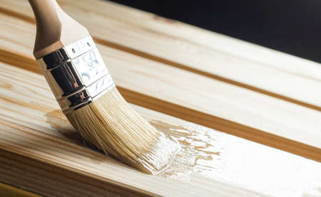 Application of varnish on a wooden surface with a brush