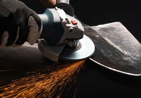 Sharpening garden shovel blade with electric angle grinder indoor