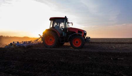 Landwirt bereitet sein Feld in einem Traktor vor, der für den Frühling bereit ist.