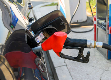 Car refueling on the petrol station with pumping gasoline fuel in car