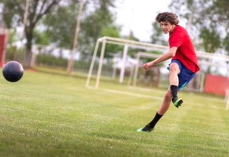 Soccer player teenager kicks ball in a goal Фото со стока