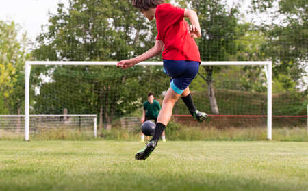 Soccer player teenager kicks ball in a goal Stock Photo