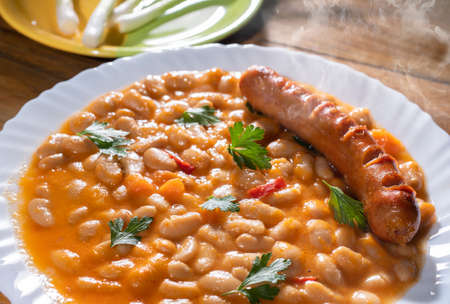 Baked beans and sausage in a white plate
