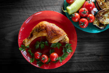Roasted chicken leg with cherry tomato.Top view.